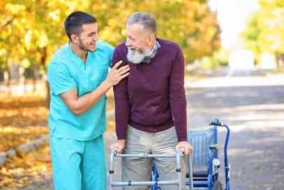 caregiver assisting the elder man as he walks