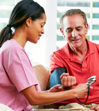 caregiver checking blood pressure of an elderly man