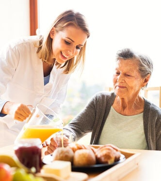 caregiver serving food to senior woman