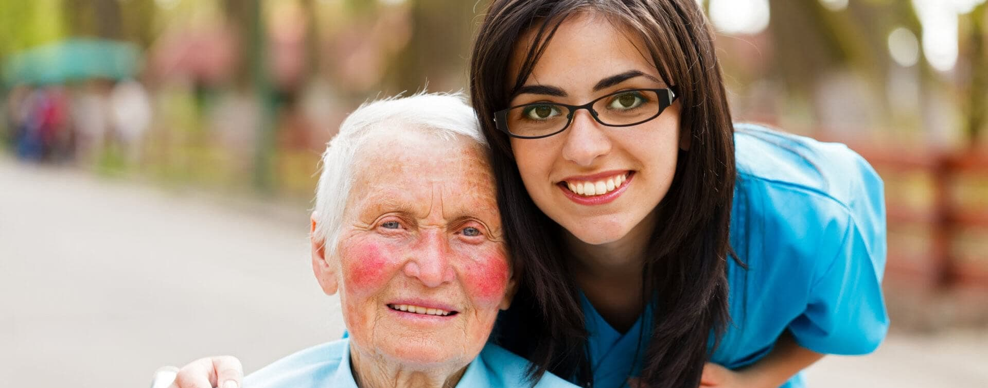 beautiful caregiver with glasses smiling with the elder woman