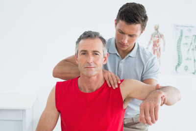 therapist stretching the arm of the elder man
