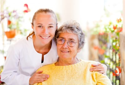 an elder woman and a kind nurse smiling