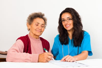 elder woman signing paper with the caregiver